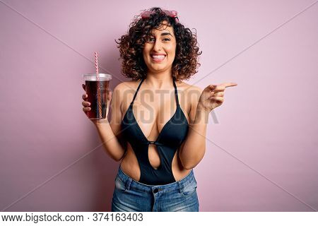 Beautiful arab woman on vacation wearing swimsuit drinking cola refreshment using straw very happy pointing with hand and finger to the side