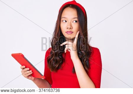 Young beautiful chinese girl holding touchpad serious face thinking about question with hand on chin, thoughtful about confusing idea