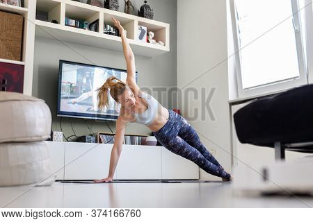 Attractive Sporty Woman Working Out At Home, Doing Pilates Exercise In Front Of Television In Her Li