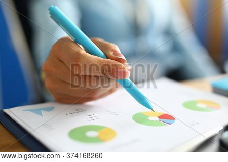 Close-up Of Businesslady Hand Holding Pen. Finance Manager Analysing Bar Charts And Graphs. Woman Wr