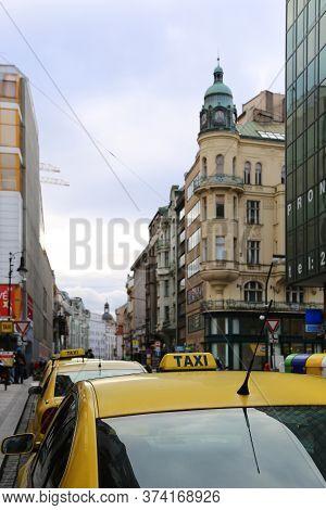 Prague, Czech Republic - November 2013: Bright Yellow Taxi Cabs On A City Street In Evening Prague