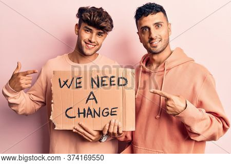 Young gay couple holding we need a change banner smiling happy pointing with hand and finger