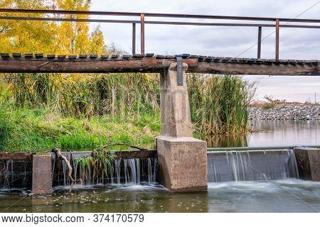 river diversion dam and footbridge - Poudre River in northern Colorado, fall scenery