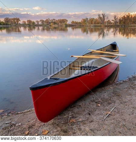 red tandem canoe with wooden paddles on a lake shore, fall scenery in Colorado
