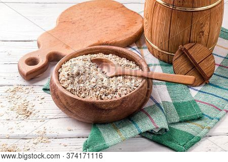 Oatmeal In A Wooden Bowl, Surrounded By Wooden Kitchen Utensils.