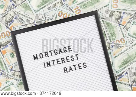 Mortgage Interest Rates Text On Letter Board With Lots Of Hundred Dollar Bills As Background. Mortga