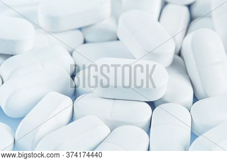 Medical Background Of Many White Capsule Tablets Or Pills On The Table. Close Up. Healthcare Farmacy