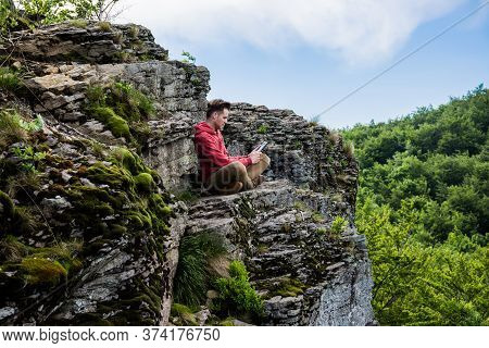 A Young Man In A Red Sweater And Beige Pants Sits On Top Of A High Cliff And Reads An E-book. Thick