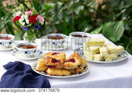 Afternoon Tea In The Garden With Scones, Strawberry Jam, Finger Sandwiches With Cucumber And Egg Sal