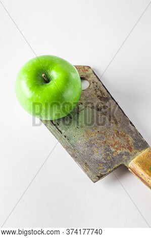 Green Apple On A White Background. An Apple Is Standing On A Kitchen Hatchet. Old Kitchen Hatchet Wi