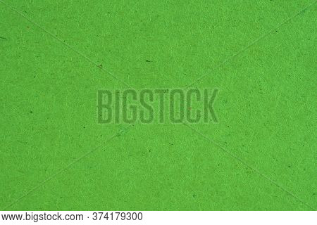The Surface Of Green Cardboard. Rough Natural Paper Texture With Cellulose Fibers. Bright Saturated