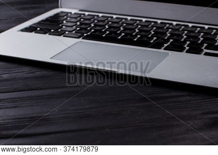 Close Up Laptop Touchpad And Keyboard. Dark Black Wooden Table Surface.