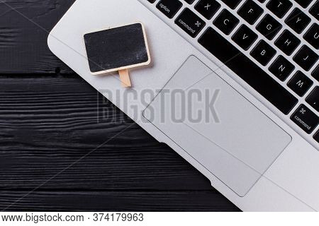 Top View Close Up Laptop Keyboard And Touchpad. Small Board With Black Screen. Dark Wooden Table Bac