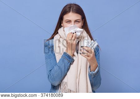 Young Caucasian Woman Has Runny And Common Cold, Holding In Hands Pills And Nasal Spray, Wearing War