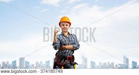 Beautiful Female Builder In Hardhat With Finger Pointing Upward. Portrait Of Young Woman In Checkere