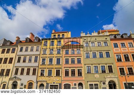 Typical colorful houses buildings with multicolored facade, outdoor porch with front steps stairs, Piwna street with cobblestone road, blue sky background, old historical city centre, Gdansk, Poland