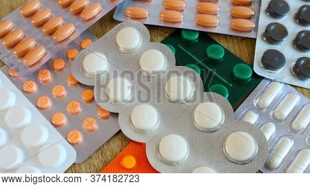 Medicines Many Tablets Of Orange White And Green In A Blister On The Table
