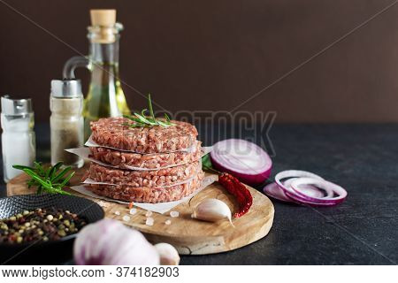 Raw Burger Cutlets Made From Minced Fresh Meet With Spices And Herbs On Black Background. Ingredient
