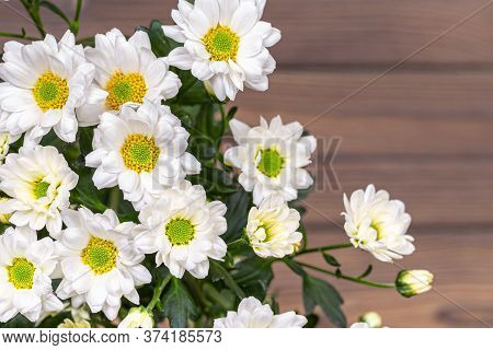 A Bouquet Of White Bush Chrysanthemums On A Wooden Table.