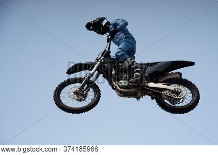 Rider In A Helmet Makes A Risky Jump In The Air On A Black Motorcycle