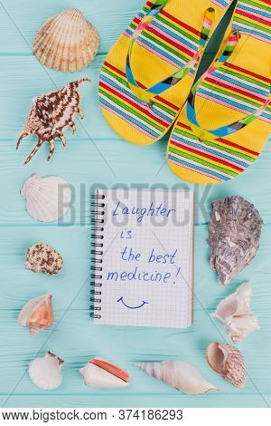 Notebook Surrounded The Perimeter Of Shells And Multicolored Slipper. Blue Wooden Background. Laught