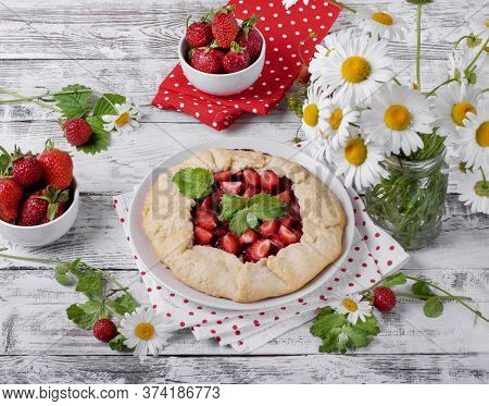 Shortbread Galette With Strawberry Surrounded By Berries And Chamomiles On The White Wooden Table