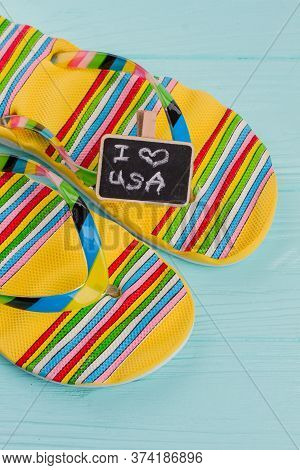 Close-up Multicolored Sandals With Chalkboard On Blue Desk. I Love Usa On Chalkboard. Rubber Bright