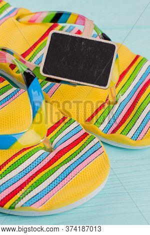 Close-up Pair Of Flip Flops On Turquoise Background. Multicolor Lines On Flip-flops.