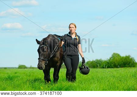 One Caucasian Woman And Her Saddled Horse Are Walking On The Grass.