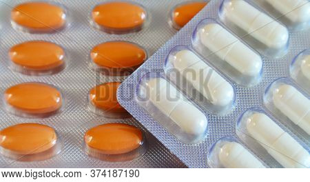 Medicines Orange Oval Pills And White Capsules In A Blister Close-up