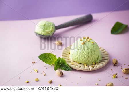 Homemade Pistachio Ice Cream With Chopped Pistachios On Bright Pink And Purple Background