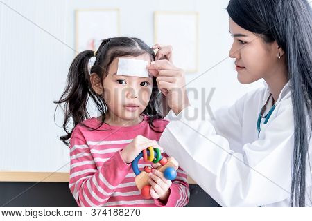 Asian Pretty Woman Doctor Is Pasting A Fever Reducing Gel Forehead Area Of A Girl Patients To Reduce
