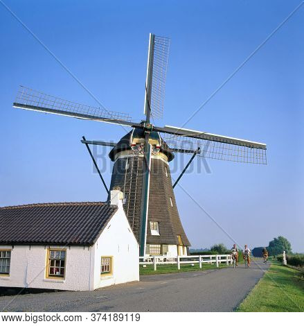 Zevenhuizen,holland-may 05,2018: Old Traditional Dutch Mill And House Of The Miller With Bikers At A