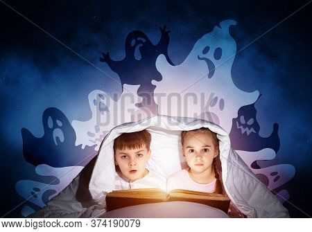 Scared Girl And Boy Reading Kids Book In Bed. Frightened Children Lying Under Blanket Together. Kids