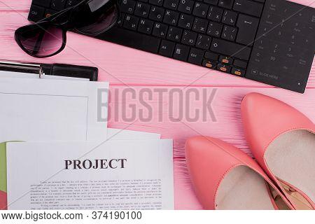 Female Workspace With Keyboard, Sun Glasses, Shoes, Different Papers On Pink Background. Flat Lay Wo