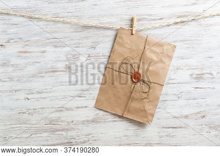 Old Paper Envelope Hanging On Rope On Wooden Background. Twine Rope With Wooden Clothespins. Brown L