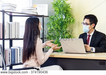 Portrait of asian business advisor giving advice to customer about financial loan situation in bank office. New normal social distance business for banking financial and investment concept.