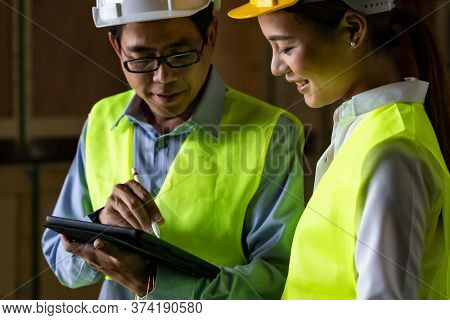 Asian warehouse manager discuss with warehouse worker using digital tablet to assign job inside distribution warehouse. Reopening business warehouse technology and logistic concept.