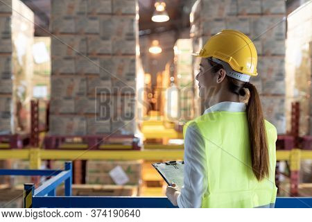Side view of asian female warehouse worker with archboard flip chart look inventory with dustrubution warehouse in background. Reopening business warehouse technology and logistic concept.