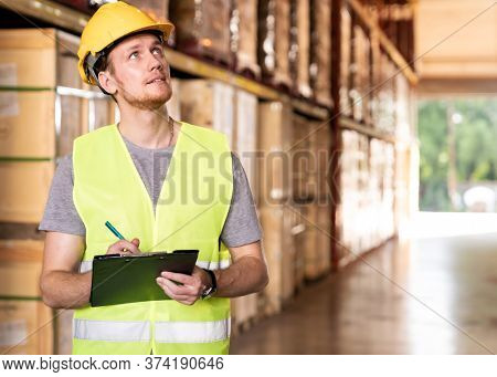 Portrait white caucasian warehouse worker stand with archboard and pen for inventory checking in large warehouse distribution center. Reopening traditonal business warehouse and logistic concept