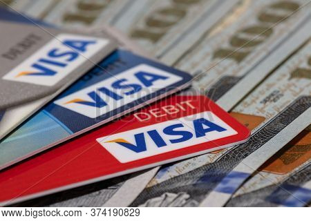 Miami, Florida - June 3, 2020: Red, blue, and silver Visa debit cards on hundred dollar bills. Some cards and bills are in soft focus. Business concept. Angled, Close-up shot. Illustrative editorial.