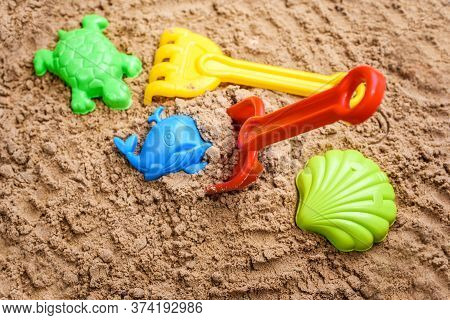 Beach Sand With Toys For The Baby, Water, The Word Summer In Colored Letters.