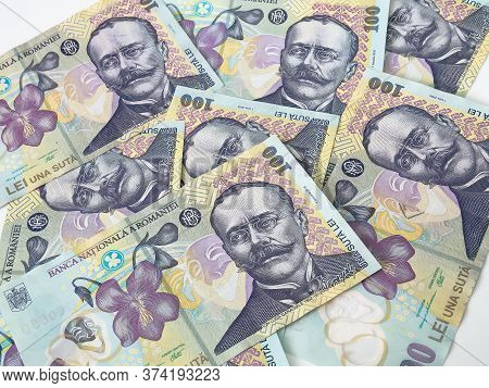Many 100 Ron Or Lei Romanian Banknotes On White Background. Romanian Currency.