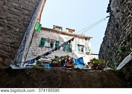 Clothes Hanging For Drying On The Clothesline In The Courtyard Of Old Stone Houses With Tiled Roofs