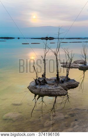Sunrise over the Dead Sea. Excess salt appears on the surface of the water. The sun is reflected in the the water of the sea. Concept of ecological, medical and photo tourism