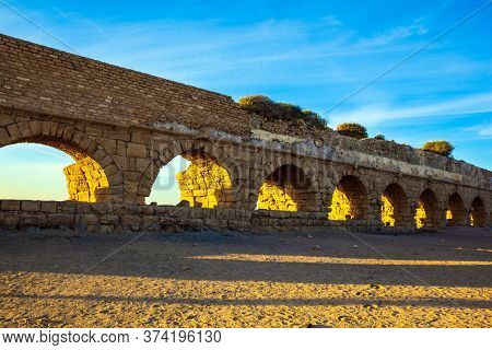 Summer in Israel. The ancient Roman aqueduct is lit by the setting sun. Long evening shadows lie evenly on the warm sand. Magical sunset in Caesarea.