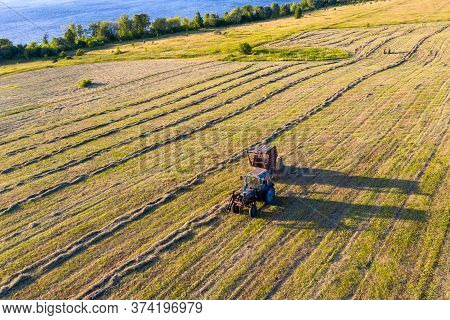 Hayfield. A Tractor On The Bank Of The River Collects Mown Hay In Bales. Shooting From A Drone.