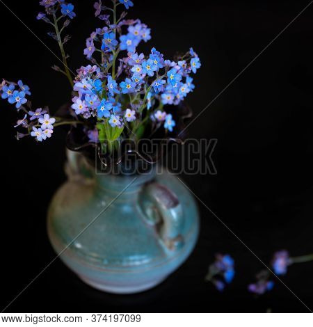 Forget-me-nots Flowers In Vase On The Dark Table