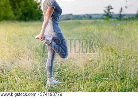 Concepts Of Evening Jogging In Nature.woman Warming Up Before Jogging.