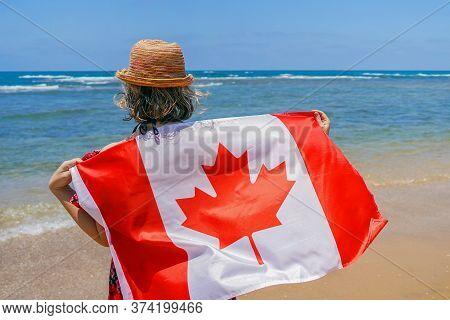 Woman In Hat With Canada Flag At The Beach. Girl Holds An Canada Flag While Standing On The Beach, B